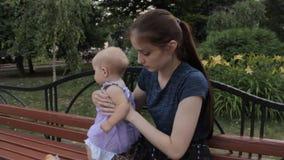 Een zeer jong kindermeisje die een babymeisje naast haar zitten en haar een plak van Stokbrood geven Het babymeisje staat op stock videobeelden