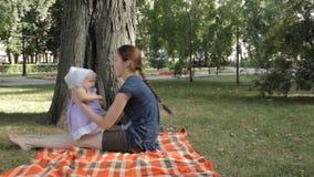 Een zeer jong kindermeisje die een babymeisje wiegen stock video