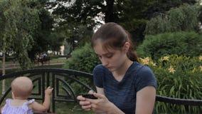 Een zeer jong kindermeisje die een oog met een vinger wrijven blijven speel een spel op smartphone stock video