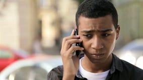Een zeer jonge tiener spreekt ernstig via mobiele telefoon stock footage