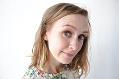 Een zeer mooi meisje met haar haar onderaan en in een kleding met bloemenpatronen bevindt zich op een witte achtergrond Een snoep Stock Fotografie