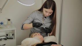 Een zeer mooi meisje in een schoonheidssalon doet een laminering geselt De schoonheidsspecialist voert de procedurewimper uit stock videobeelden