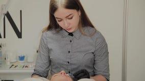 Een zeer mooi meisje in een schoonheidssalon doet een laminering geselt De schoonheidsspecialist voert de procedurewimper uit stock video