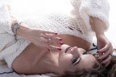 Een zeer mooi wit-haired meisje met lange wimpers en rode manicure in een witte gebreide sweater ligt op het bed sexy Stock Afbeelding