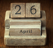Een zeer oude houten uitstekende kalender die de datum 26ste April tonen Stock Foto's