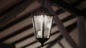 Een zeer oude retro lantaarn glanst binnen op het plafond stock videobeelden