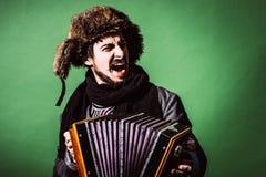 Een zeer positieve mens met harmonika het stellen in de studio stock foto