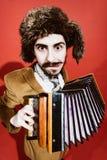Een zeer positieve mens met harmonika het stellen in de studio royalty-vrije stock foto's