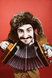 Een zeer positieve mens met harmonika het stellen in de studio stock afbeelding