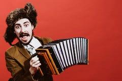 Een zeer positieve mens met harmonika het stellen in de studio stock afbeeldingen