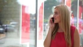 Een zeer prettige vrouw die haar mobiele telefoon op de straat met behulp van stock footage
