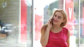 Een zeer prettige vrouw die haar mobiele telefoon op de straat met behulp van stock video