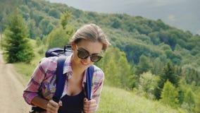 Een zeer vermoeide vrouwentoerist met een rugzak gaat de bergweg uit Wilskracht en fysieke duurzaamheid stock footage
