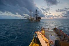 Een zeeschip tijdens het slepen verrichting van een olieplatform stock afbeelding