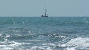 Een zeilboot die in het golvende overzees overgaan stock footage