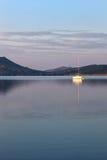 Een zeilboot die in het meer bij zonsopgang nadenken Royalty-vrije Stock Afbeeldingen