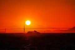Een zeilboot en een veerboot die San Francisco Bay kruisen bij zonsondergang met Golden gate bridge op de achtergrond Royalty-vrije Stock Foto's