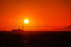 Een zeilboot en een veerboot die San Francisco Bay kruisen bij zonsondergang met Golden gate bridge op de achtergrond Royalty-vrije Stock Afbeeldingen