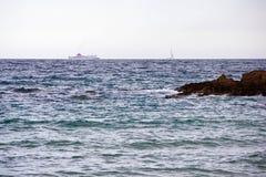Een zeilboot en een veerboot van de kust van Lloret de Mar Stock Foto