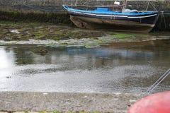 Een zeilboot legde at low tide tegen een zeedijk vast stock afbeelding
