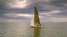 Een zeilboot vaart op een meer met hierboven wolken stock videobeelden