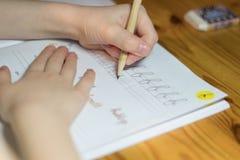 Een zes éénjarigenmeisje praktizeert schrijvend in een notitieboekje stock foto's