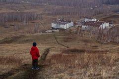 Een zes-jaar-oud kind in een rood onderaan jasje bevindt zich op een weg buiten de stad en onderzoekt de afstand royalty-vrije stock foto's