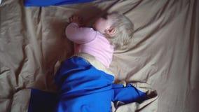 Een zet de leuke kleine gewekte peuterrotaties rond in een blauwe deken, dan zijn kant aan en bevriest Weinig Meisje van de Baby stock videobeelden