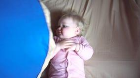 Een zet de leuke kleine gewekte peuterrotaties rond in een blauwe deken, dan zijn kant aan en bevriest Weinig Meisje van de Baby stock video
