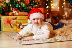 Een zeven-jaar-oude jongen ligt op een zachte pluizige deken op zijn maag en schrijft een brief aan Santa Claus Kerstmis royalty-vrije stock foto's