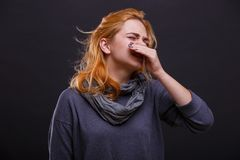 Een ziek meisje in een grijze sjaal niest tegen een zwarte achtergrond royalty-vrije stock foto