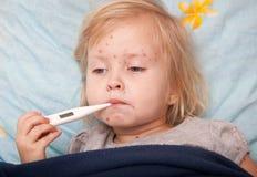 Een ziek meisje meet de temperatuur stock foto's