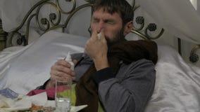 Een zieke mens ligt in een bed met een warme sjaal rond zijn hals, bespat een geneeskunde in de neus Neus Nevel Langzame Motie stock video