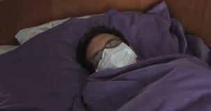 Een zieke mens in een wit masker ligt in bed in de kliniek tijdens een besmetting epidemie stock footage