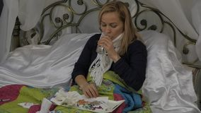 Een zieke vrouw ligt in een bed die zijn neus blazen zoals hebbend een lopende neus tijdens een koude of een griep Langzame Motie stock video