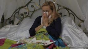 Een zieke vrouw ligt in een bed met een warme sjaal rond zijn hals, die zijn neus blazen zoals hebbend een lopende neus tijdens e stock video