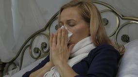 Een zieke vrouw ligt in een bed met een warme sjaal rond zijn hals, die zijn neus blazen zoals hebbend een lopende neus tijdens e stock footage