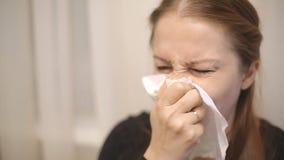 Een zieke vrouw op middelbare leeftijd niest en blaast haar neus in een zakdoek stock footage
