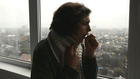 Een zieke vrouw in sweater kijkt uit het venster en hoest stock footage