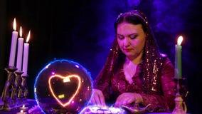 Een zigeuner in de magichsky salon is op een kristallen bol benieuwd en een hartteken verschijnt daarin stock videobeelden