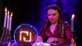Een zigeuner in de magichsky salon is op witte stenen benieuwd en een sjekelteken verschijnt in de kristallen bol stock videobeelden