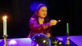 Een zigeuner in de magische salon is bezig geweest met magisch met een kristallen bol, waarvan elektrische gloed en lichte kaarse stock videobeelden