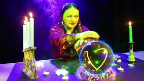 Een zigeunervrouw in de magichsky salon is bij de kristallen bol benieuwd en een glanzend hart verschijnt daarin stock video