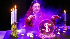 Een zigeunervrouw in een magische salon in rookwolken van rookgissingen op een kristallen bol en een dollarteken verschijnt daari stock video