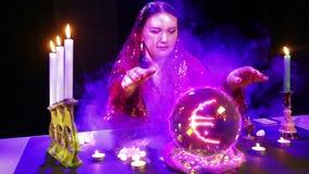 Een zigeunervrouw in een magische salon in rookwolken van rookgissingen op een kristallen bol en een euro teken verschijnt daarin stock video