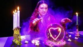 Een zigeunervrouw in een magische salon in rookwolken van rookgissingen op een kristallen bol en een hartteken verschijnt daarin stock video