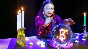 Een zigeunervrouw in een magische salon veronderstelt op een kristallen bol en een bitcointeken verschijnt daarin stock video