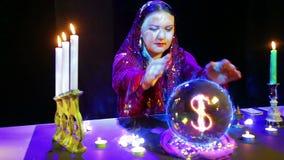 Een zigeunervrouw in een magische salon veronderstelt op een kristallen bol en een dollarteken verschijnt daarin stock video