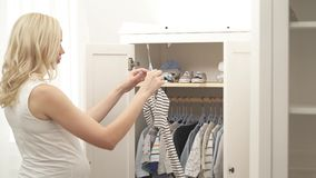 Een zijaanzicht van een zwanger blonde die zich voor de geopende garderobe bevinden Zij kijkt over baby'skleren en verbetert stock footage