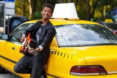 Een zijaanzichtportret van veelvoudige raskerel in vrijetijdskleding dichtbij gele uitstekende auto, spel bij gitaar, op de straa stock foto